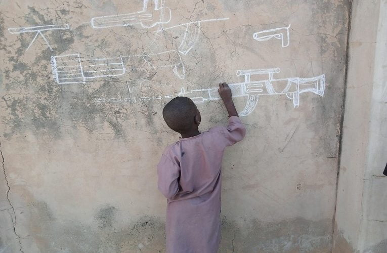 'This is sad'- Nigerians react to photo of little boy drawing a gun on the wall in Yobe